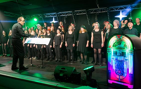 Chor auf der Bühne mit bunt leuchtender Jukebox davor